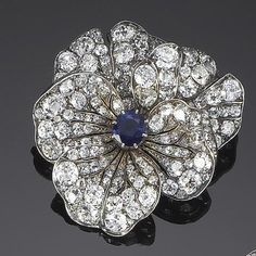 A late 19th century sapphire and diamond flower brooch, circa 1880 The unfurling pierced petals, set throughout with old brilliant and rose-cut diamonds, with a cushion-shaped sapphire stamen, mounted in silver and gold