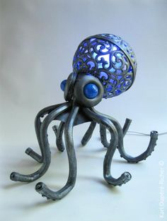 Octopus lamp : My latest creation is this mood lamp in form of an octopus. This lamp is made from an assembly of found objects, such as a suspended globe, garden hoses, a distributor of candy, Christmas balls, caps and a plastic container.