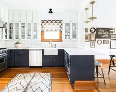 Mid-sized farmhouse u-shaped open concept kitchen idea in Seattle with a farmhouse sink, shaker cabinets, gray cabinets, white backsplash, subway tile backsplash, stainless steel appliances, medium tone hardwood floors, a peninsula, quartzite countertops and brown floors