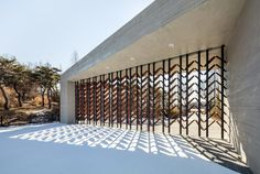 This South Korean museum is dedicated to teaching visitors about wood and features moving timber screens set into its concrete facades.