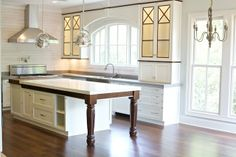 Drool!! Alabama white marble on island. Walnut trim around white cabinets.  Arched window over sink.