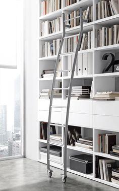Eck-Bücherschrank und Schubladen St._6 in Lack matt bianco candido, seitlich Tisch Poker in Eiche grau. Leiter aus Metall mit Halterung und Lauf auf der..
