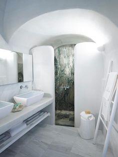 CHARME MEDITERRANEO A SANTORINI: FINITURE PREZIOSE Superfici preziose nel bagno. Due varianti di marmo, una chiara e una scura, fanno da sfondo alla doccia e alla toilette in muratura con doppio lavabo ad appoggio.