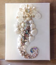 Seahorse Fantasy is handmade here at Sea Things with all natural in color Seashells. Painted White Canvas base to the Beautiful Seashell Seahorse Wall Decoration. This little Seahorse is handmade with