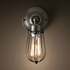 """Often used as factory lighting, caged sconces provided space-saving illumination while protecting the bulbs they housed. Handcrafted wire lamp Dark pewter finish Dimensions 5""""W x 4""""D x 11""""H 13 cm W..."""