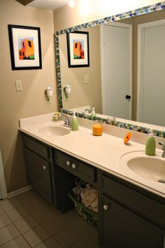 Tile frame around mirror. I would use a chair rail and stain it to match the cabinets and make it look mire like a picture frame.