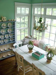 Nooks & Crannies - wooden table, big windows with a bench in front and a hutch / wall shelves filled with plates. All in pastels.