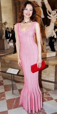 Olga Kurylenko wearing a pink knit Azzedine Alaia gown with a fishtail hem, accessorized with a jeweled statement necklace and red clutch.