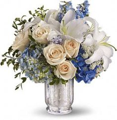 Beautiful hydrangea and delphinium in varying shades of blue, crème roses, white lilies and Queen Anne's lace are accented with pitta negra and eucalyptus and delivered in an exclusive antiqued Mercury Glass Vase.