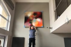 """My gallerist from Gallery 713 / Knokke/ BE hard at work, showing one of my latest paintings in the home of a customer. """"Hideaway""""/ 140 x 130 cm /sold."""
