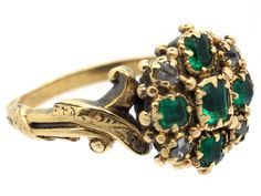 A lovely late Georgian cluster ring set with emeralds and diamonds. The shank is particularly nice as it has swirly tendrils in the gold design. It has a small locket section behind the cluster which would most likely have held a lock of hair. It was made circa 1820.