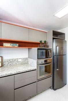 A cozinha contemporânea com atmosfera leve quebra a neutralidade do cinza e do inox com o uso do laranja nos nichos e ao redor dos armários. O projeto é dos arquitetos Sergio Valliatti Jr e Luciana Patrão