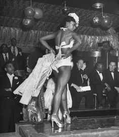 Contestants parading for judges for the costume prize during the Urban League Ball. Photograph by Yale Joel. New York City, February 1949.