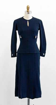 Skirt Suit: ca. 1930's, custom made of checkered thin stretchy wool, tailored blouse with keyhole neckline, Art Deco buttons, skirt with pleated panels for a flared out fit.