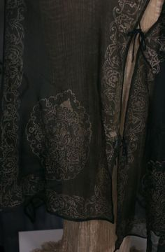 Mariano Fortuny Gauze Sleeveless Coat, Fortuny's treatment of this shape included cutting it open in the front.For these tunic shaped coats he used fine gauzes or crepes which he printed his patterns on.these tunics can be sleeveless, short sleeved or long sleeved, they are usually trimmed with silk cords and glass beads.