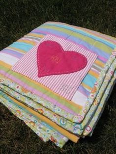 Sew a heart at the bottom of their quilts with their info embroidered. Baby clothes quilt back
