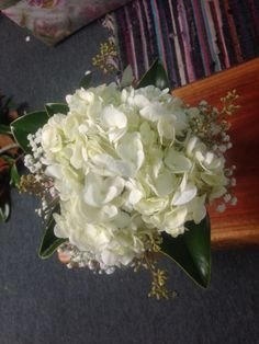 One white hydrangea with a touch of magnolia, babies breath and seeded eucalyptus.