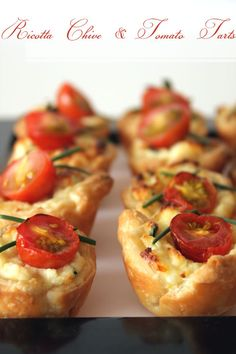 ricotta chive & tomato tarts  •1 sheet of bought shortcrust pastry (or 1.5 sheets if you can't be bothered re-rolling the scraps)  •125g of ricotta  •50g of tasty or cheddar cheese  •1 tablespoon freshly cut chives plus longer pieces to decorate, 40x roughly 1 inch pieces  •1 egg  •10 dainty cherry tomatoes, cut in half  •1 mini cupcakes/tart baking tray with holes lightly greased with butter