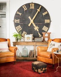A weathered clock face hung on Paris's Boulevard Saint-Germain in the late 1800s acts as a statement piece in the living room.   - CountryLiving.com