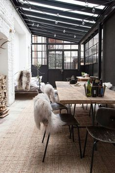 Elegant and cozy dinging room in a large winter garden with a large wooden table, black metal chairs and faux fur. We love the chain of lights!