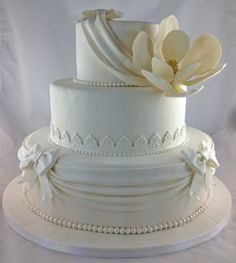 Wedding cake with a southern theme - pearls, magnolia, lace and drapes.