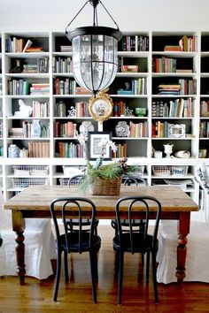 A Christmas Home Tour (dining room/library, bookshelves, farmhouse table, slipcovered chairs, greenery + pinecones, lantern)