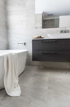 Red Lily Renovations - Perth. 1200x300 Porcelain tiles.  Petite bath by Reece bathrooms.  Wood look vinyl wrap doors. Wood Vanity. Stone benchtop.  Fully frameless mirror.  Rectangle basin.