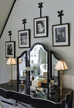 Bedroom converted into glam black and white vintage closet. Black and white closet with glossy white textured wall and ceiling paired with glossy black moldings. Glossy black Hollywood Regency vanity with brass lamps paired with white tufted vanity chair.