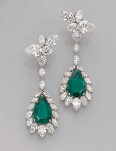A pair of emerald and diamond ear pendants by Harry Winston. Each designed as a detachable pendant set with a pear-shaped emerald within a marquise-cut diamond surround to the pear-shaped and marquise-cut diamond cluster surmount, 7.0 cm long. With maker's mark of Jacques Timey for Harry Winston.