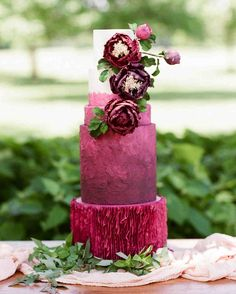 Wedding Cake Design Ideas That'll Wow Your Guests   Martha Stewart Weddings - The crepe-like base tier of this wedding cake is only one unique part of the dessert's overall look. Textured fondant and three major blooms bring the drama up top. #weddingcakes #weddingideas #weddingcaketopper