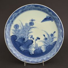 A Japanese Blue and White Porcelain Dish with a a Steep Narrow Rim, Arita Kilns c.1690-1720. Decorated with a Landscape with Flowering Plants and Grasses. The Border with Further Flowering Plants. The Back with Single Flower-Heads and the Base with an Apocryphal Chenghua Mark (Ming 1465 - 1487).