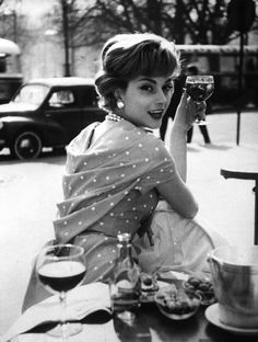 French fashion model Marie-Helene Arnaud sitting at a cafe. Photograph by Loomis Dean. Paris, March 1957.
