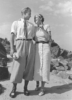 Sommar vid stranden, Sandkaas på Bornholm. Man och kvinna i ledig fritidsklädsel står sida vid sida och håller om varandra, ser varandra djupt i ögonen och ler. 1936. Foto: Gunnar Lundh. CC-BY.