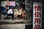 Men playing chinese chess in front of a sex shop in an old street of Beijing, China