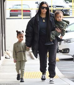Mom on duty: Kim held North's hand while carrying her one-year-old son Saint during their ...