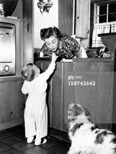 In her kitchen, American actress and swimmer Esther Williams getting a candy from her son Ben Gage Jr. 1950s (Photo by Mondadori Portfolio by Getty Images)