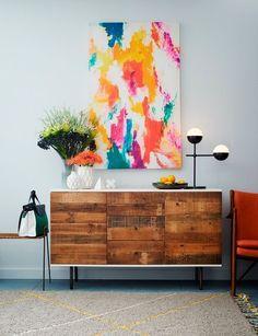 Consolas y cuadros en zonas de paso: madera y arte moderno