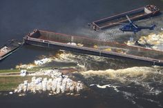 2013.06.18 - A helicopter dropped supplies at a levee breach in Fischbeck, Germany, Monday. A third cargo barge has been sunk there to try and close the breach, which has caused flooding and forced evacuations. (Jens Wolf/European Pressphoto Agency)