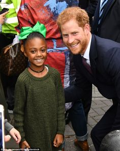 Cheerful Prince Harry poses for a photo with an adorable youngster on a visit to the Support4Grenfell community hub