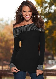 off-the-shoulder black sweater with dual gold-teethed zippers at each side.
