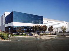 Nave industrial, oficinas en el frontal, en edificio acristalado anexo.