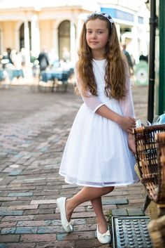 This stunning girls party dress is hand made in 100% cotton with anti static polyester lining. The dress has layers of netting and spot tulle trimmed with the same fabric and has a button and loop opening at the back and a detachable sash. This girls dress with 3/4 length spot tulle sleeves is perfect for any special occasion and makes the perfect bridesmaid dress, flower girl dress or communion dress . Available in ivory or cream in standard length or ballerina length.From £99 #flowergirl