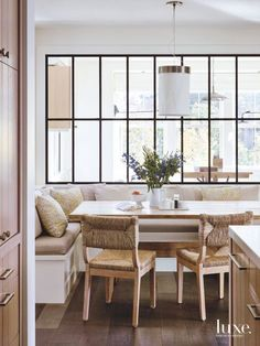 Carson appointed the kitchen's breakfast area with an antique Swedish table from Galerie Half and rush-and-oak dining chairs by Michele Bönan for Chelini. The pendant is custom and showcases a linen shade with a satin-nickel trim.