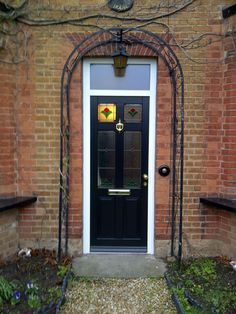 Black wooden front door with stained glass window