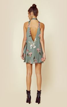 """This fun and flirty mini dress by Show Me Your Mumu features a high neck sleeveless silhouette, low back, pretty floral allover print, and a slinky satine fabrication.   Made in USADry Clean Only100% Poly SatineFit Guide:Model is 5ft 7 inches; Bust: 34"""", Waist: 25"""", Hips: 35""""Model is wearing a size XSRelaxed FitShoes Featured Not Available For Purchase"""
