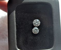 Here is my 1 carat moissanite and my 1.5 carat diamond (GIA, excellent cut, E color, SI1) side by side.    I don't see much of a difference except that my diamond is a bit more sparkly and the moissanite reflects rainbows in the sun.    And sometimes in the light, it's a little bit more warm/yellowish toned.