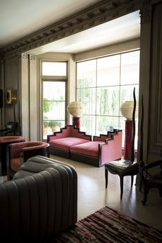A pink daybed flanked by a pair of urns on pedestals