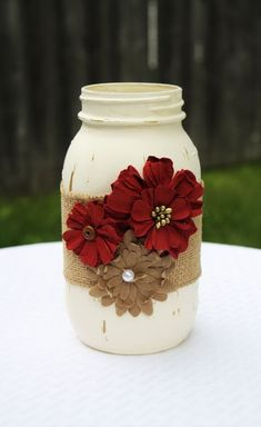 This gorgeous mason jar would be a lovely addition to your home. Use it alone as a cute home accent, or utilize it as a stylish container! This jar is painted in vintage white and is embellished with burlap ribbon and paper flowers. Each jar is painted Red Mason Jars, Burlap Mason Jars, Distressed Mason Jars, Bottles And Jars, Mason Jar With Flowers, Vintage Mason Jars, Christmas Mason Jars, Mason Jar Projects, Mason Jar Crafts