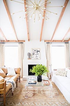 Neutral living room with vaulted, beamed ceilings, sputnik chandelier and fireplace