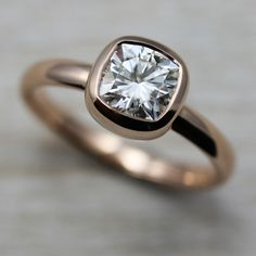 Our ethical 6mm Cushion Cut Engagement Ring, pictured in recycled 14k rose gold with an eco-friendly Forever Brilliant Moissanite. With a shiny, polished finish.